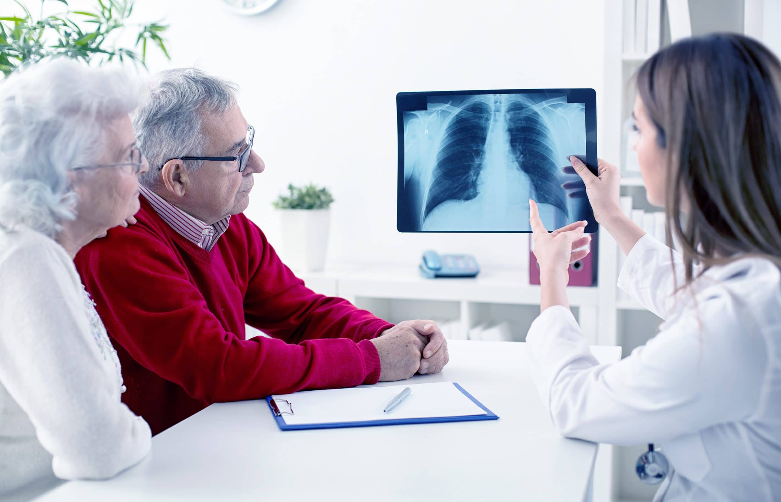 This is an image of a doctor diagnosing a patient with lung cancer via scan imagery.