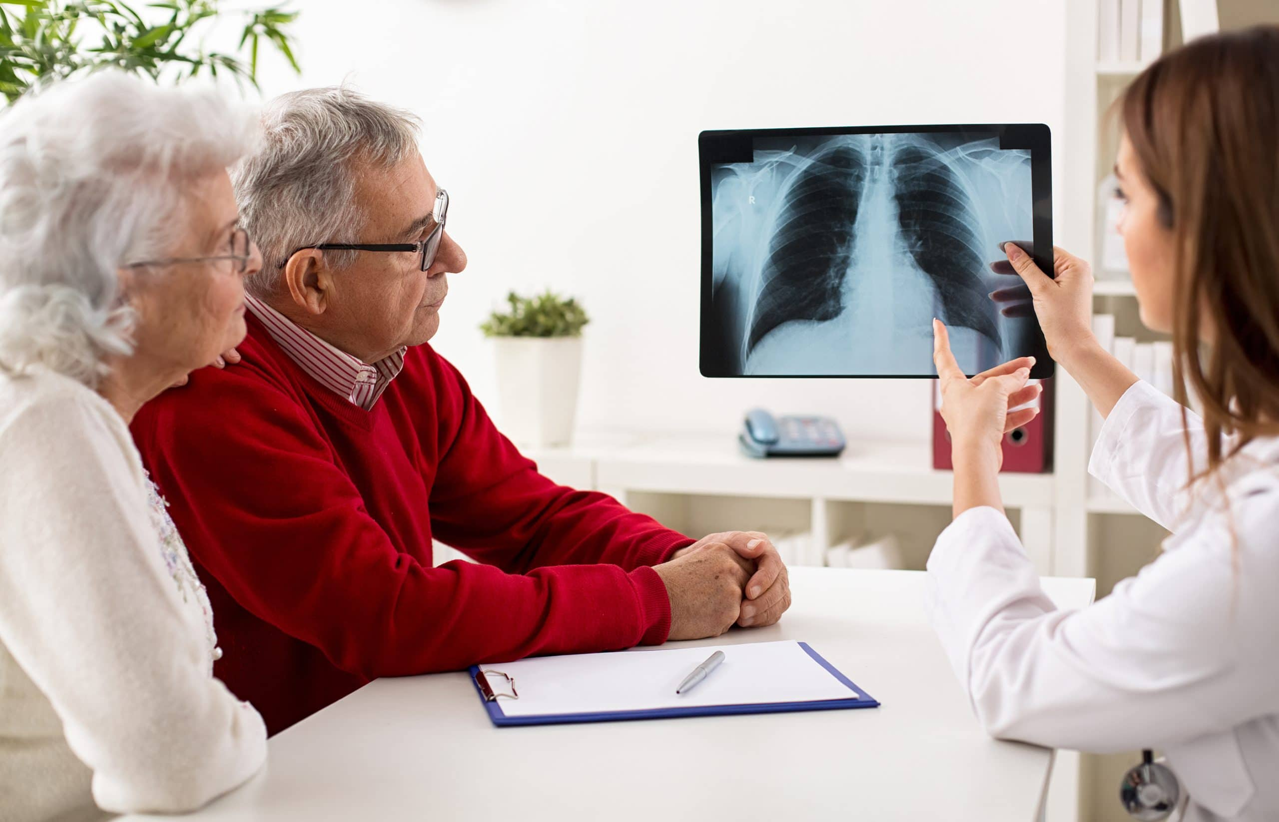 This is an image of a doctor showing a patient their pleural mesothelioma x-ray results.