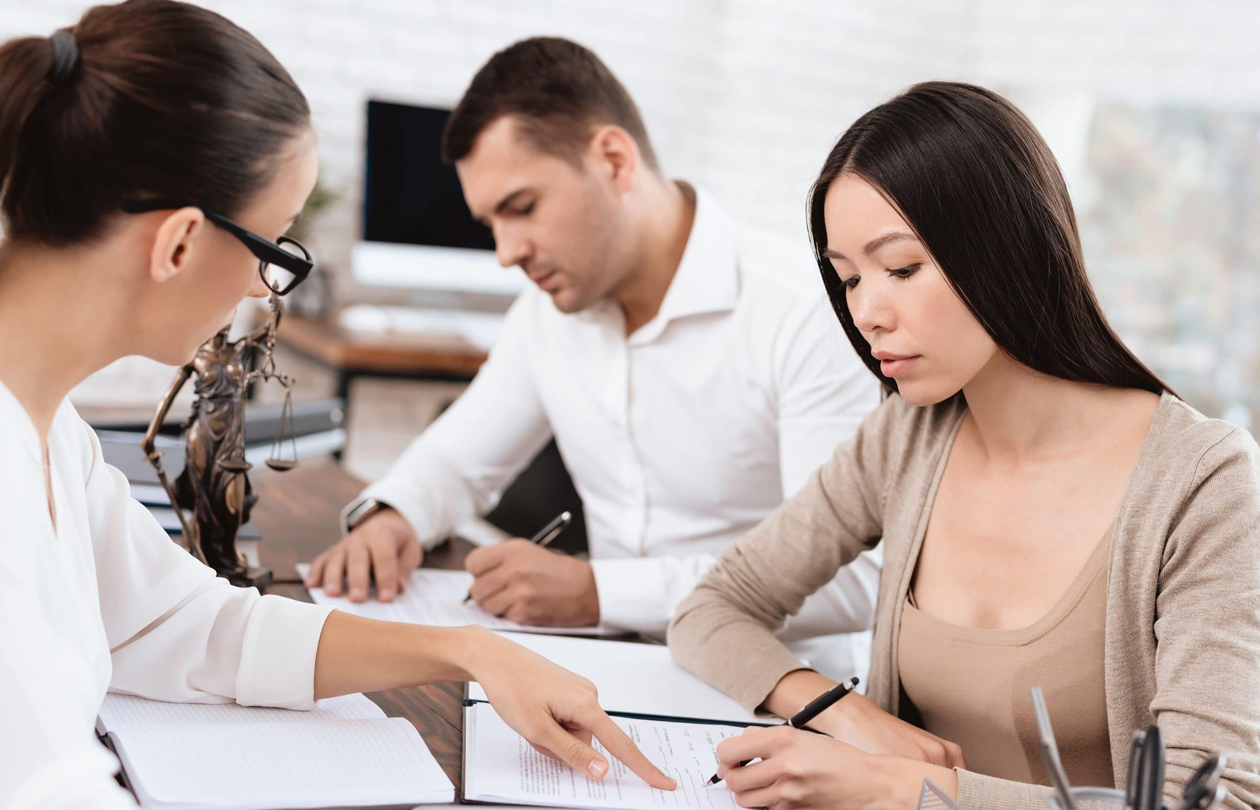 This is an image of a lawyer working with clients and agreeing on a settlement.