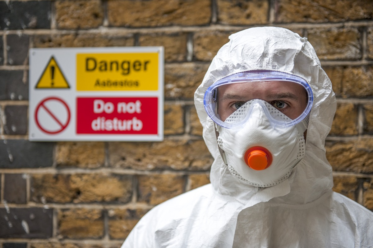 asbestos personal protective equipment covering hair and nose and mouth with warning danger sign in the background