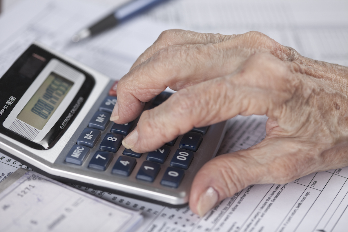 senior woman's hand doing financial work with calculator