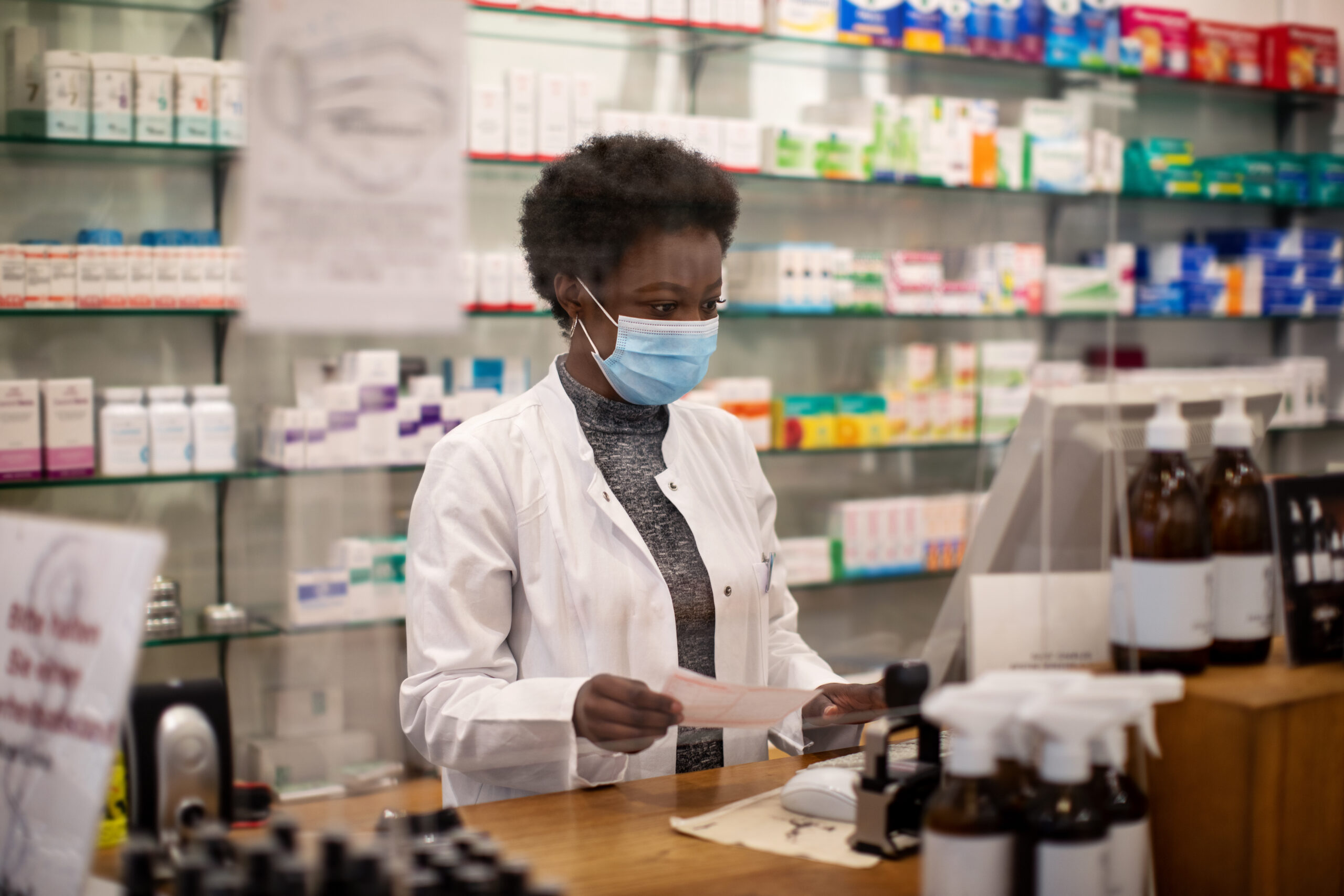 Woman pharmacist with face mask working in a drug store
